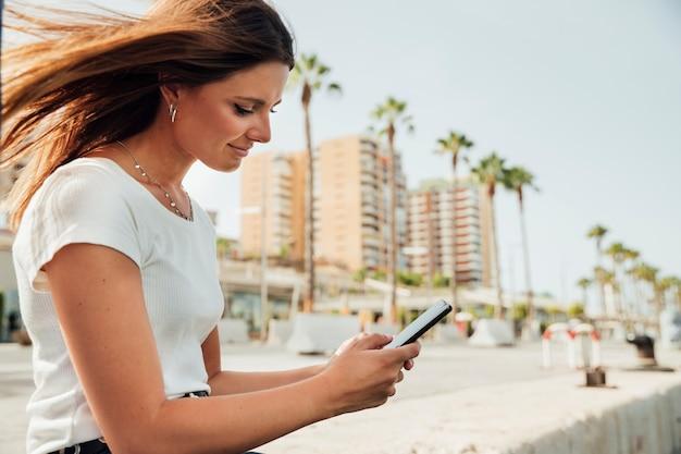 横向きの女性が彼女の電話を見て 無料写真