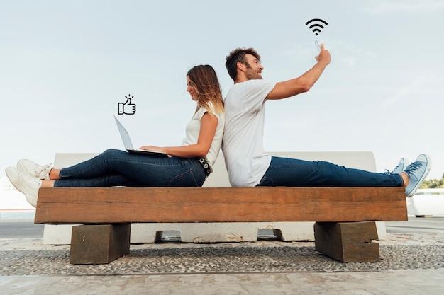 ソーシャルメディアを使用してベンチにカップルします。 無料写真