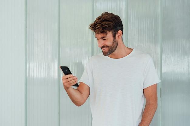 Человек с белой футболкой держит телефон Бесплатные Фотографии