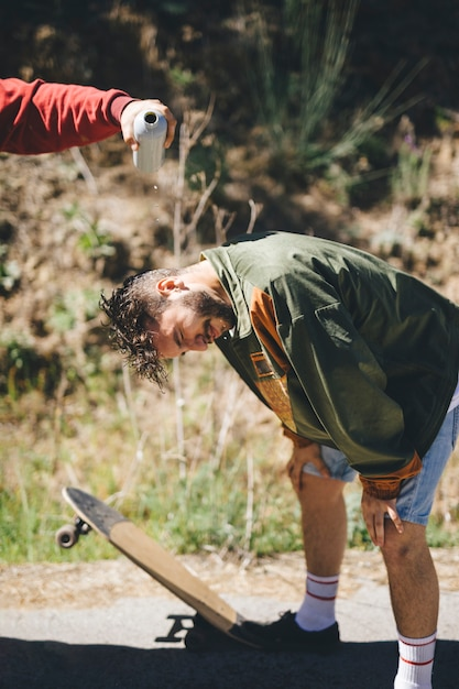 友人の頭に水を注ぐ男 無料写真