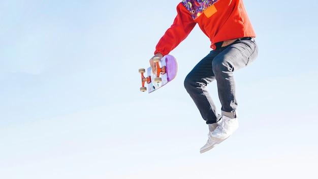 スケートボードでジャンプ男のミディアムショット 無料写真