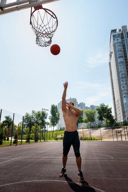 ハンサムな男がボールを投げるロングショット 無料写真