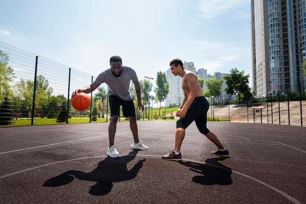 都市のバスケットボールのロングショットをして幸せな男性 無料写真