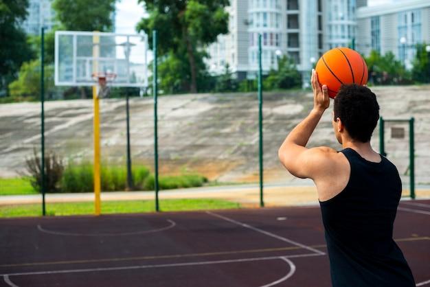 バスケットミディアムショットで投げるアメリカ人男性 無料写真