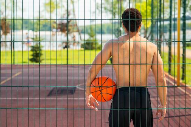 男はボールを保持し、フープを見て 無料写真