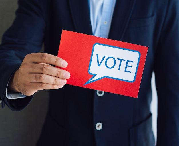 カメラに赤い投票を示す男 無料写真
