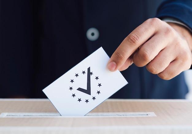 ボックスのクローズアップで投票を置く男 無料写真