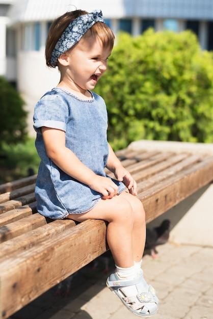 ベンチに小さな女の子の側面図 無料写真