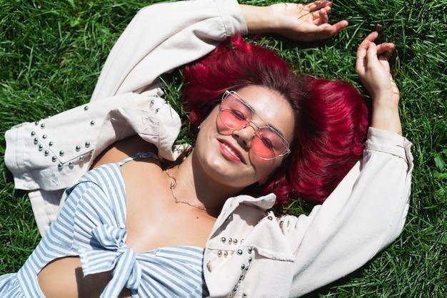 Средний снимок женщины, лежащей в траве Бесплатные Фотографии