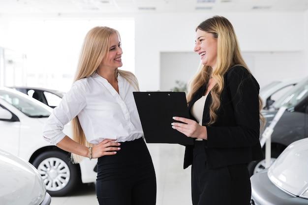 車の取り引きを締める女性 無料写真