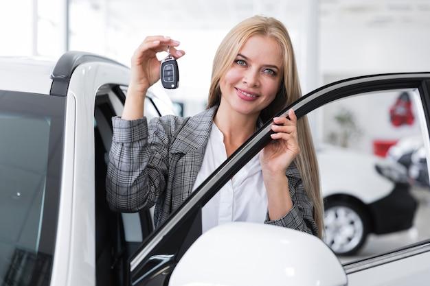 車のキーを保持している女性の正面図 無料写真