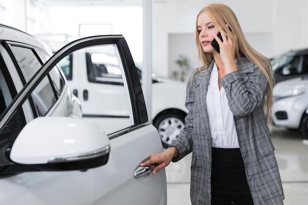 電話で話していると車のドアを開く女性 無料写真