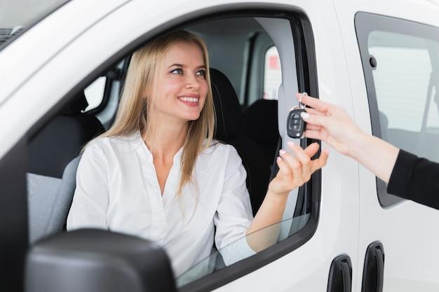 車のキーを受け取る笑顔の女性とのクローズアップショット 無料写真