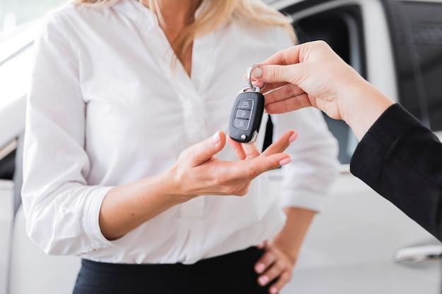 車のキーを受け取る女性のクローズアップビュー 無料写真