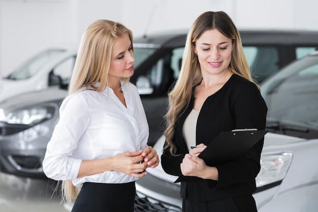 車のショールームで議論するエレガントな女性 無料写真