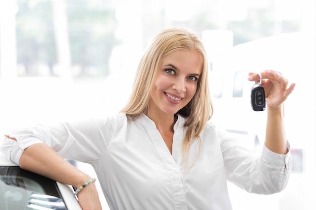車のキーを示し、カメラを見て女性 無料写真