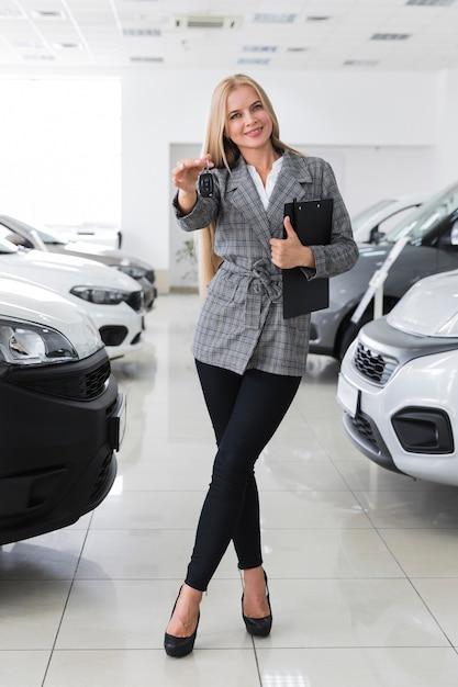 車のキーのロングショットを保持している幸せな女 無料写真