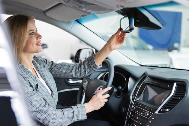車の鏡で見える幸せな女 無料写真
