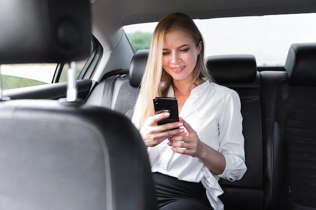 Деловая женщина сидит в машине и смотрит на телефон Бесплатные Фотографии