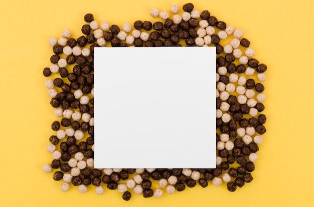 チョコレートシリアルに囲まれたコピースペースを持つ白いカード 無料写真