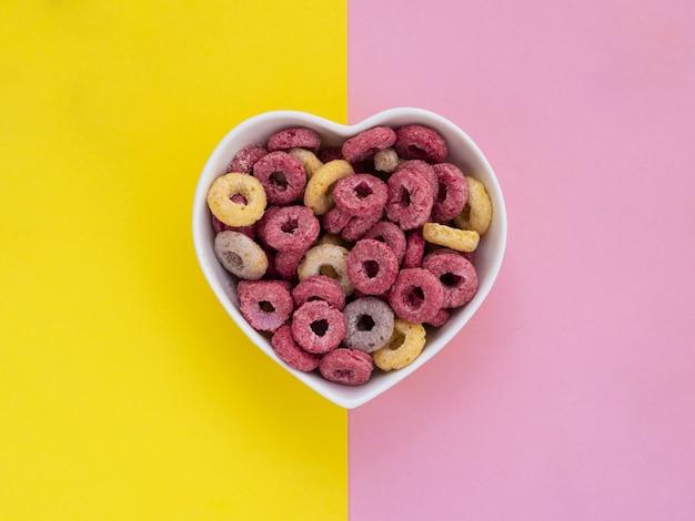ピンクと黄色のフルーツループで満たされたハート形のボウル 無料写真
