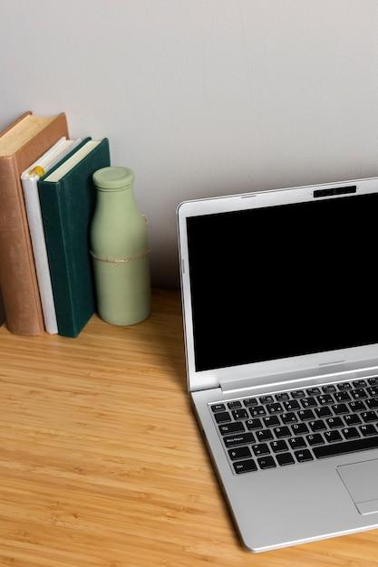 木製の机の上の本と灰色のラップトップ 無料写真