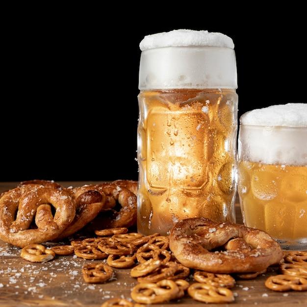 Крупным планом пиво с пеной и кренделями Бесплатные Фотографии