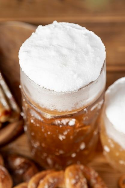 テーブルの上の泡とビールのおいしいマグカップ 無料写真