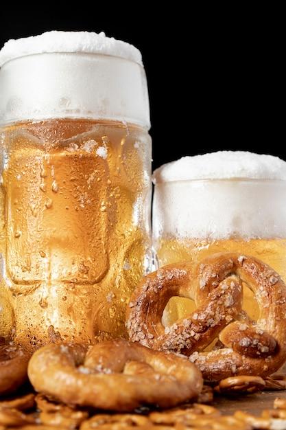 泡とプレッツェルとビールのクローズアップマグカップ 無料写真