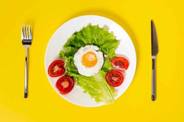 Плоское яйцо кладет друга с овощами блюдо со столовыми приборами на фоне Бесплатные Фотографии