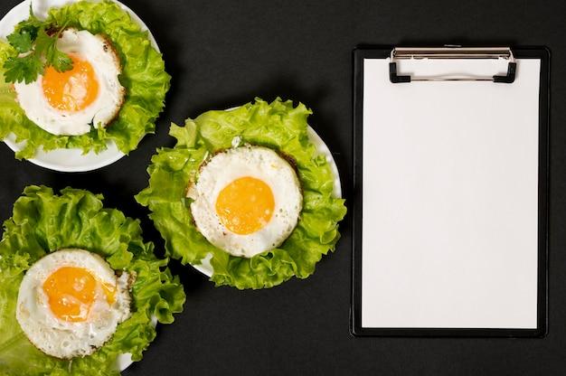 朝食の手配の横にあるクリップボードのモックアップ 無料写真