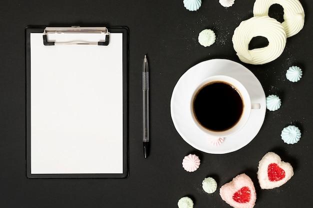 一杯のコーヒーとメレンゲクッキーを備えたモックアップクリップボード 無料写真