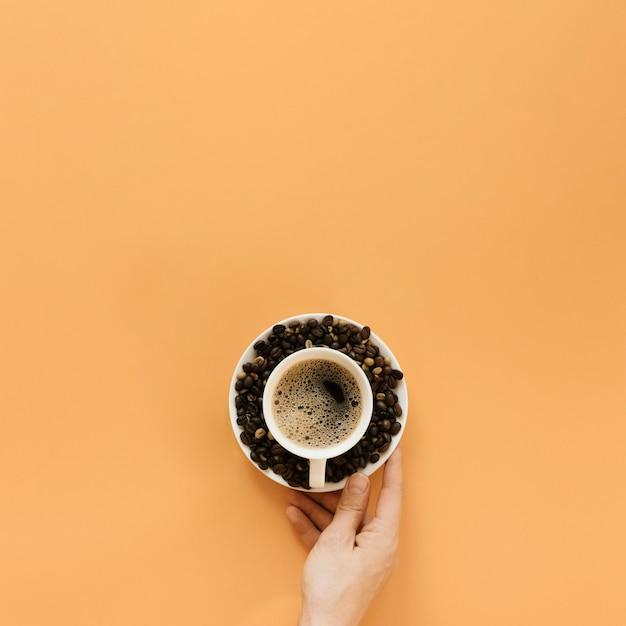 Рука держит тарелку с чашкой кофе Бесплатные Фотографии