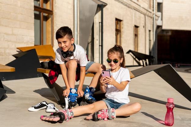 少年とインラインスケートを持つ少女 無料写真