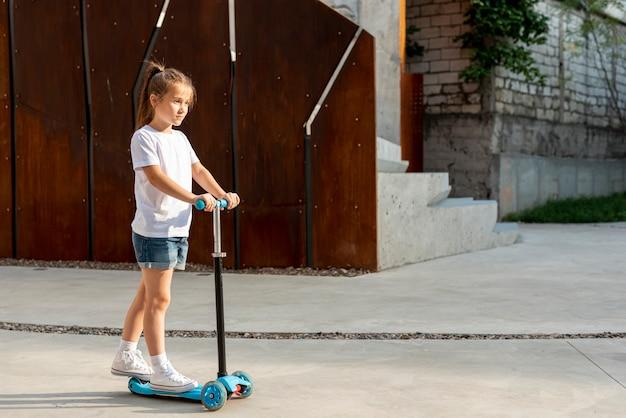 青いスクーターに乗っている女の子の側面図 無料写真