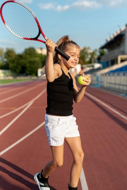 テニスラケットを持つ少女の正面図 無料写真