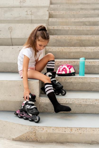 ローラーブレードを持つ少女の側面図 無料写真