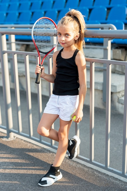 テニスラケットとボールを持つ少女の完全なショット 無料写真