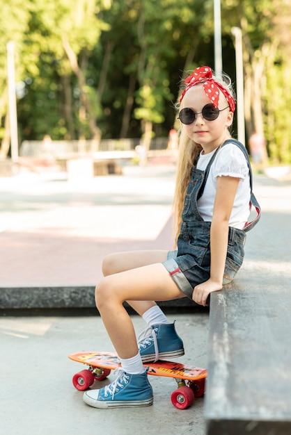青いオーバーオールの女の子の側面図 無料写真
