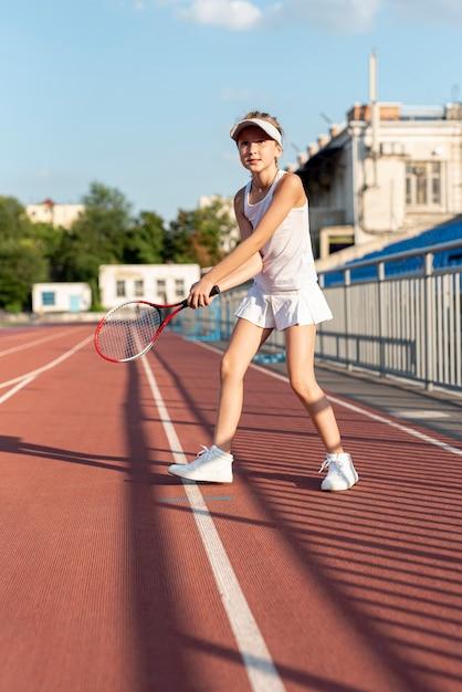 テニスラケットを持って女の子の正面図 無料写真