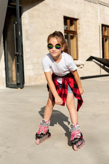 ローラーブレードを持つ少女の正面図 無料写真