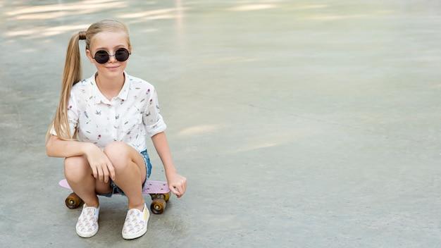 スケートボードの上に座って白いシャツの女の子 無料写真