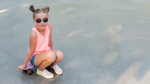 スケートボードに座っている女の子の正面を争う 無料写真