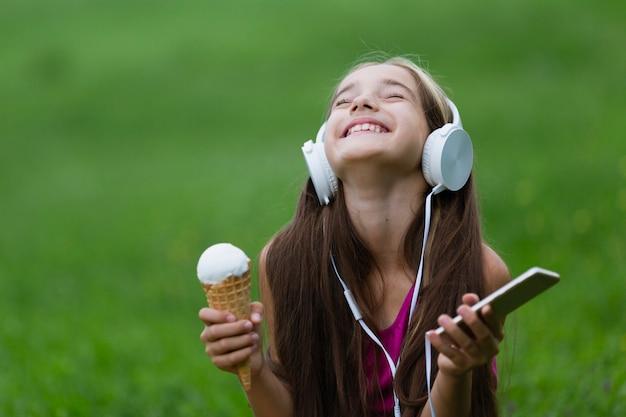 バニラアイスクリームと電話を保持している女の子 無料写真