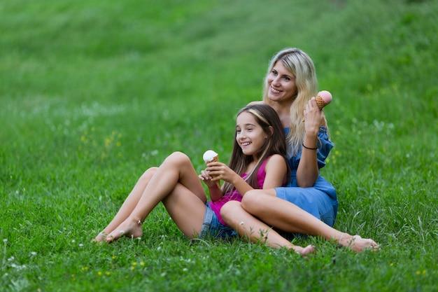 Мать и дочь лежат в траве с мороженым Бесплатные Фотографии
