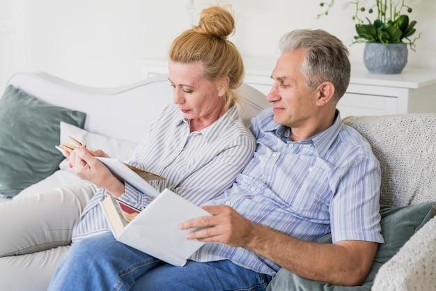 ソファで本を読んで年配のカップル 無料写真