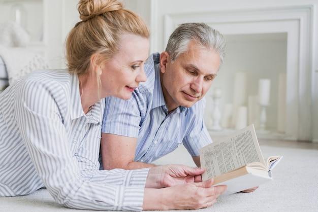 Крупным планом пожилая пара читает книгу Бесплатные Фотографии