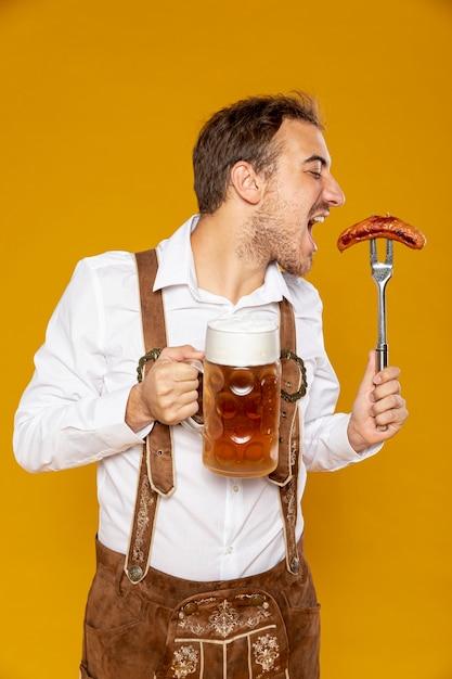 ビールパイントとソーセージを持つ男 無料写真