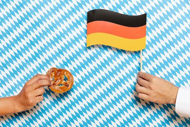男と女のプレッツェルと旗を保持 無料写真