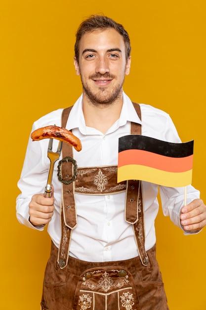 Вид спереди мужчина держит колбасу и флаг Бесплатные Фотографии